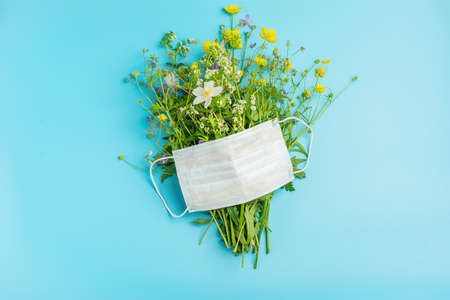 Protective medical mask and fresh flowers on a blue background. Flat layout with place for text and your design. The concept of health and the end of the pandemic