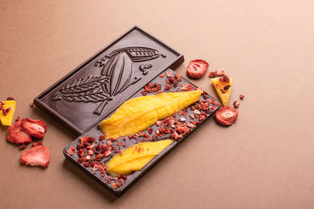 Chocolate dark Belgian bar with the addition of fruit slices of strawberry mango on a brown background. Dessert food concept. Horizontal frame copy space