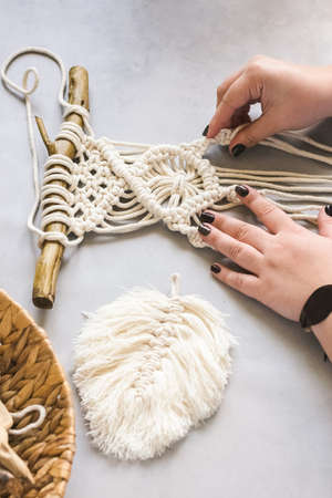 Female hands weave macrame the home workshop. Boho lifestyle. Hobby hobby concept. Selective focus Standard-Bild
