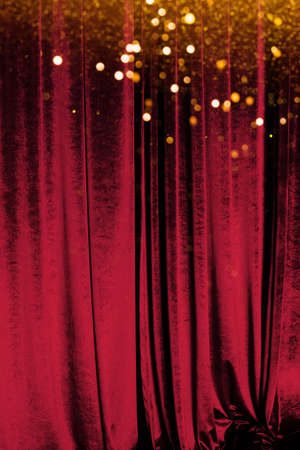 The red curtain made of luxurious velvet on the stage of the theater is fantastically glittering
