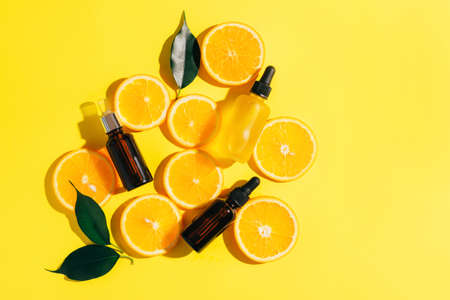A bottle of cosmetic product oil serum gel made from a juicy ripe orange on a bright yellow background