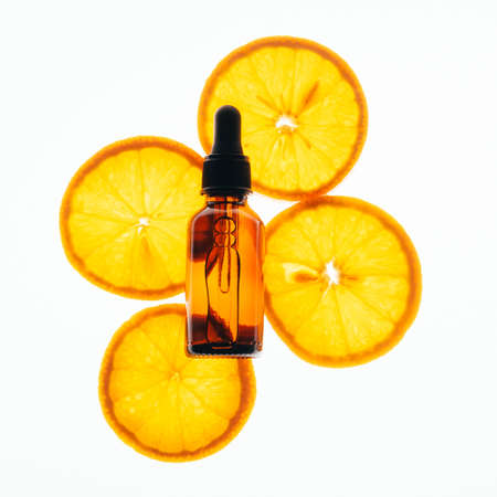 Bottle of cosmetic product oil serum gel made from juicy ripe orange white background