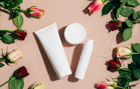 Cosmetic cream gel serum white bottle on a background of water and fresh flowers 免版税图像
