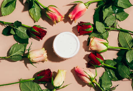 Cosmetic cream gel white bottle on a background of water and fresh flowers