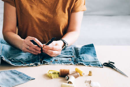 Woman repairs sews reuses fabric from old denim clothes economical reuse 免版税图像