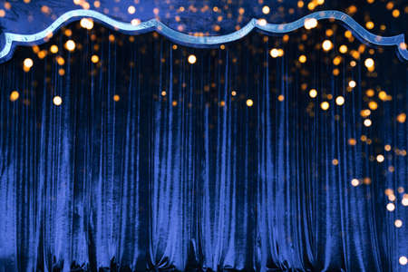 The blue curtain made of luxurious velvet on the stage of the theater is fantastically glittering