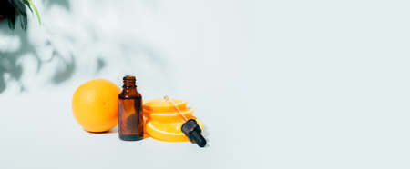 Cosmetic products gel serum oilanti-cellulite remedy from a juicy ripe orange in various bottles on a blue background sunlight hard shadows.