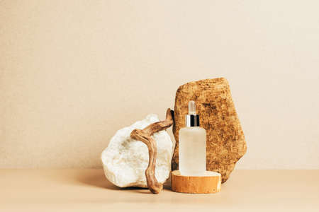 Bottle of cosmetic product oil serum pastel brown background abstract podium