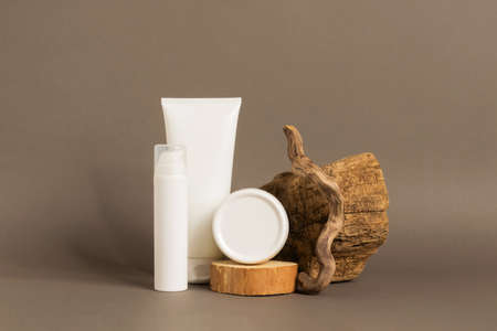Cosmetics oil serum gel in various white packaging bottles tubes on a pastel brown background modern abstract podium