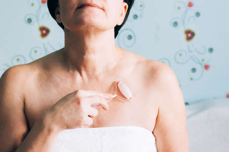 A woman in a white towel makes a relaxing Gua sha massage. Adult woman skin body care concept, alternative medicine and cosmetology home