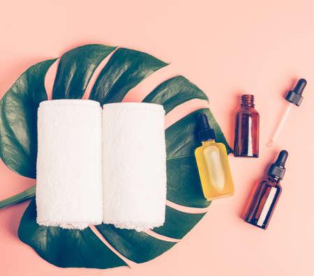 Various cosmetics oil serum gel green leaf of tropical plant clean towels on pink pastel background 免版税图像