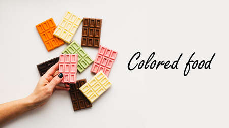 A female hand holds chocolate of various colors on a light background. Colored food text