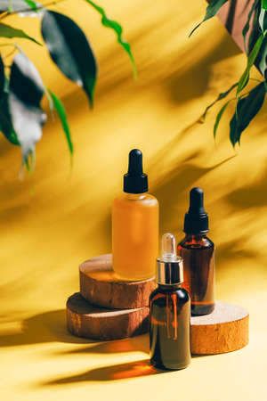 Cosmetics for face body for SPA procedures. Aromatherapy essential oil gel serum on wooden podiums yellow background