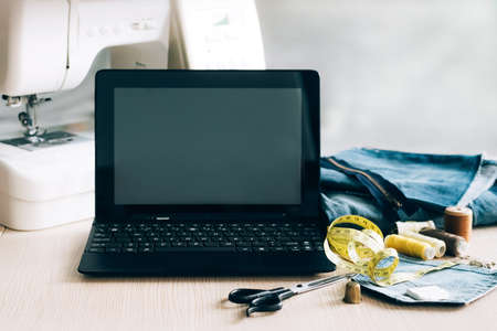 Concept for online learning and watching a sewing lesson on a laptop. Template for advertising sewing clothing repair courses