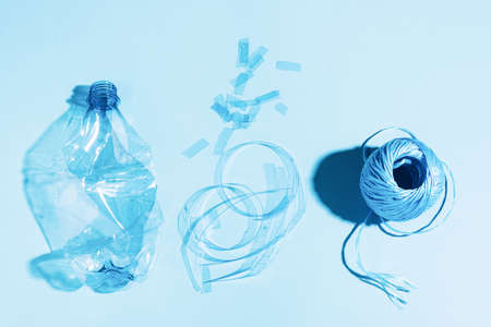 The concept recycling plastic. Empty plastic bottle recycled polyester fiber recycled products against blue background Reklamní fotografie