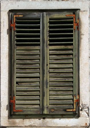Old window shutters with fading green paint photo