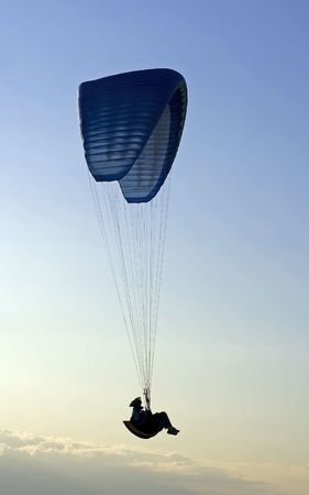 Silhouette of a paraglider in mid-air action photo