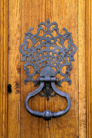 sturdy: Wrought iron knocker on a sturdy oak timber door
