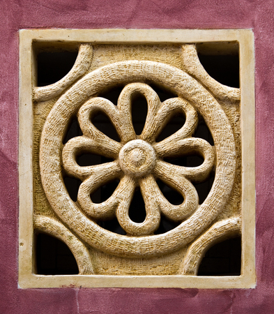 Small rose window imitation with carved floral ornaments