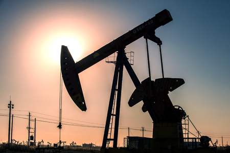 Oil pumps are running in the sunset at the oil field. On the Bohai coast of China
