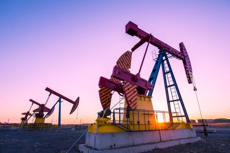 Oil pumps are running in the sunset at the oil field. On the Bohai coast of China.
