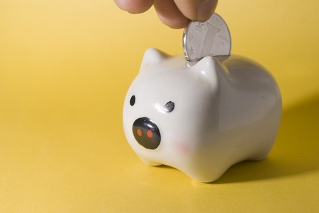 Piggy bank being loaded. yellow background photo