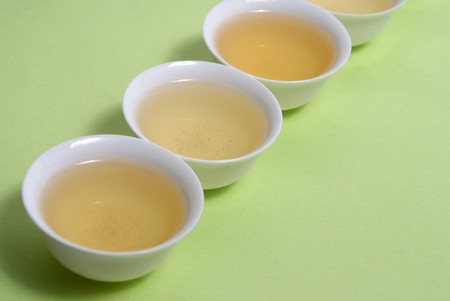 White Cup of tea side view isolated on green photo