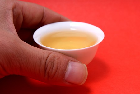 White Cup of tea side view isolated on red photo