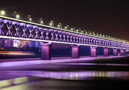 Night time at double deck bridge at Wuhan Yangtze River Bridge. It's famous for travel. Many people come to relax at evening time. In this area have park for relax. Stock Photo