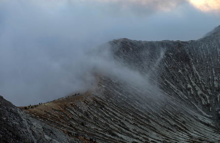 Many Tourist hiking to the top of the Kawah Ijen Volcano, At the morning time, delicate of the volcano texture.