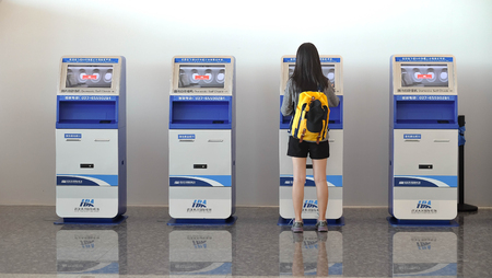 Wuhan China, Tianhe  - September 10, 2018: Young woman using the check-in machine at the airport getting the boarding pass.