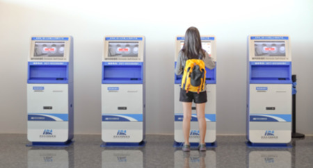 Wuhan China, Tianhe  - September 10, 2018: Young woman using the check-in machine at the airport getting the boarding pass. It's blur picture. Editorial