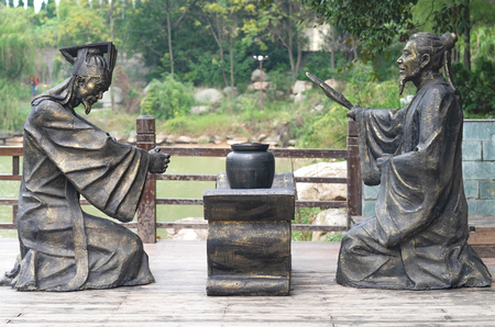 """Chibi, Hubei/ CHINA - OCT 25, 2018:The ancient battle field of The red cliff(Chibi Stone Inscription),  It's one of scene in the Chinese  movies """" The Red Cliff"""". The person  statue about the Three kingdom novel."""
