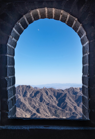 View from the fortress of The great wall along the mountain, view from window of the fortress. The China's famous landmark buildings.