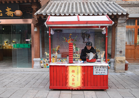 Luoyang, HenanChina - JAN 20, 2016. The Unspecific man who sell the sweet fruit with the Chinese style. He sell at the ancient road in the village for traveller.