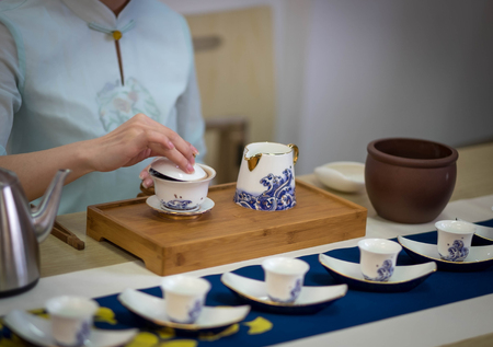Chinese tea ceremony set the show for exchange student, It's a ancient ceremony of China. Focus onlu on the cup of tea.
