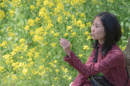 WUHAN-HUBEICHINA, MAR 28-2019: Wuhan East Lake Sakura Garden. Unspecific woman looking at the yellow flower in her hand at the east lake park. Its one of the destination for travel.