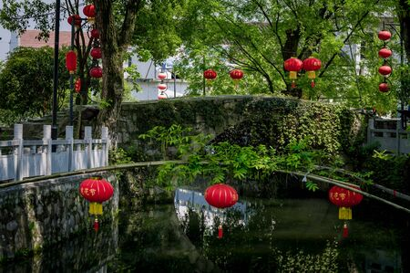The red Chinese lantern is located on the green tree, Huangshi City, Hubei province, China. This city is famous for the Iron ore mine in China.