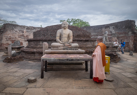 Polonnaruwa, Sri Lanka - 7 AUGUST 2019. Unspecific monk standing at the Polonnaruwa Vatadage - ancient Buddhist structure. Unesco ancient city of Polonnaruwa, one of the destination for travel, Sri Lanka