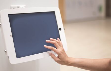 Tablet computer on woman hand in the coffee shop with blurred background.