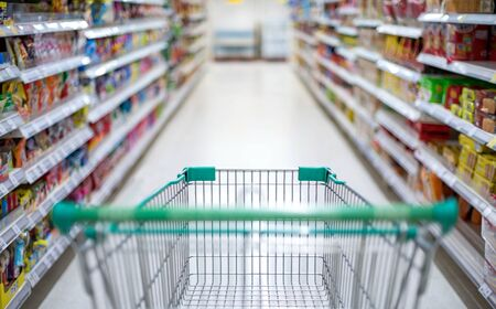 Blurred effect in the Supermarket aisle with empty silver and green shopping trolley, Shopper choosing the food in supermarket Panic buyer for hoarding food, Coronavirus Covid-19 concept. Reklamní fotografie