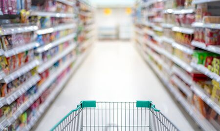 Blurred effect in the Supermarket aisle with empty silver and green shopping trolley, Shopper choosing the food in supermarket Panic buyer for hoarding food, Coronavirus Covid-19 concept. Archivio Fotografico