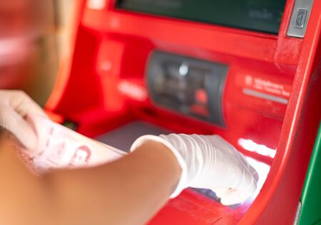 Female hands to press the ATM key in the red cabinet.  Finger   pressing a pin code on a number pad. Security code on an red automated teller machine (ATM). Foto de archivo