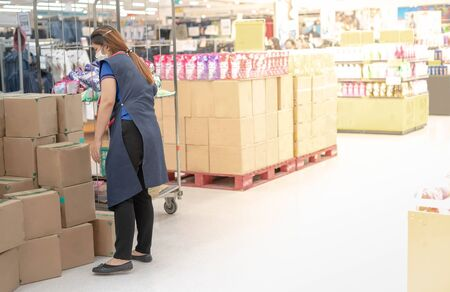 The woman employer wear surgical mask and uniform stocks shelves with checking inventories in supermarket for report about the inventory.