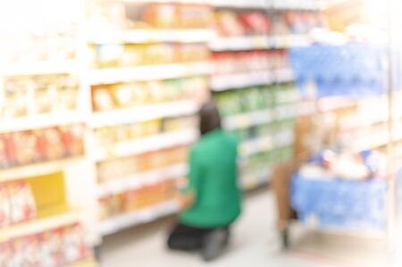 Blurred effect in the Supermarket employer wear surgical mask and uniform stocks shelves with checking goods for report about the inventories.
