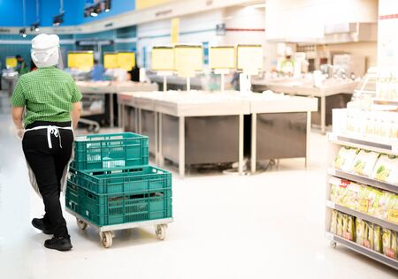The back view of supermarket employer wear apron and uniform pushing the tray on the cart for check goods stocks shelves and report about the inventories.