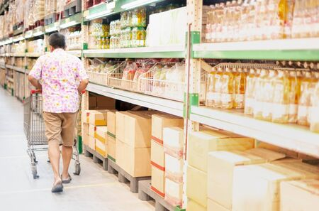 The back view man pushing shopping trolley prepare foods and drink for stockpiling in the warehouse superstore. Stock Photo
