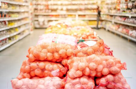The pile of onion in net bag put on the floor for wholesale customer in the foods and vegetarion in part of wholesale store market.