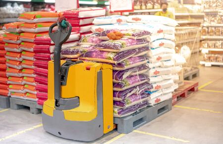 Hand pallet truck with the rice bag and plastic pallets with goods in the wholesale market. Unloading products for the supermarket. Trade and logistics.