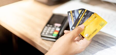 Hand holding credit card and credit card machine, The credit card prepare for customer and entrepreneur using for online shopping, e-commerse, business and internet banking with laptop. 写真素材